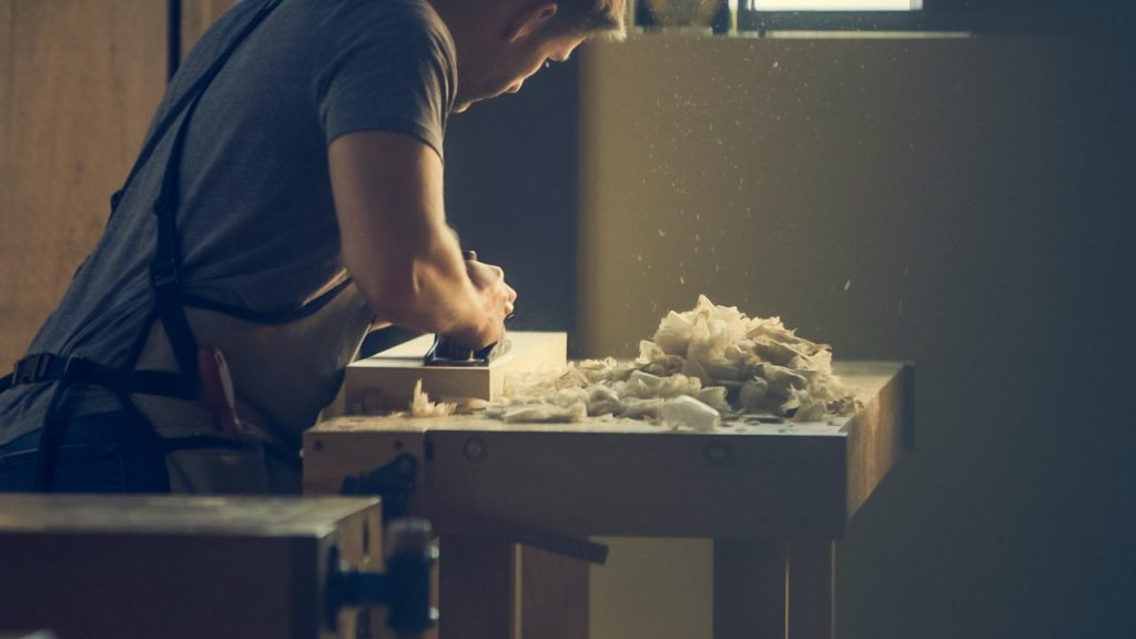 man working wood on work table