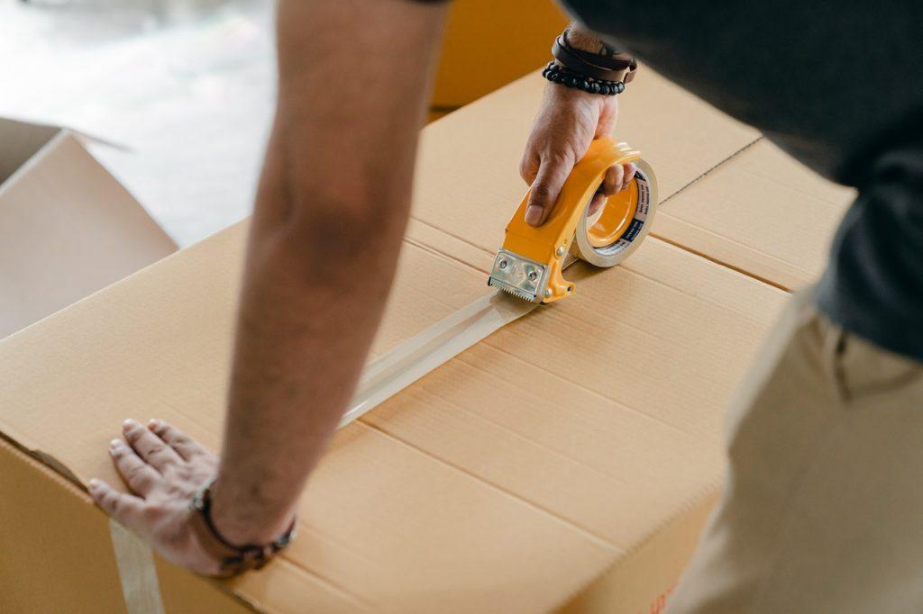 man taping a box shut