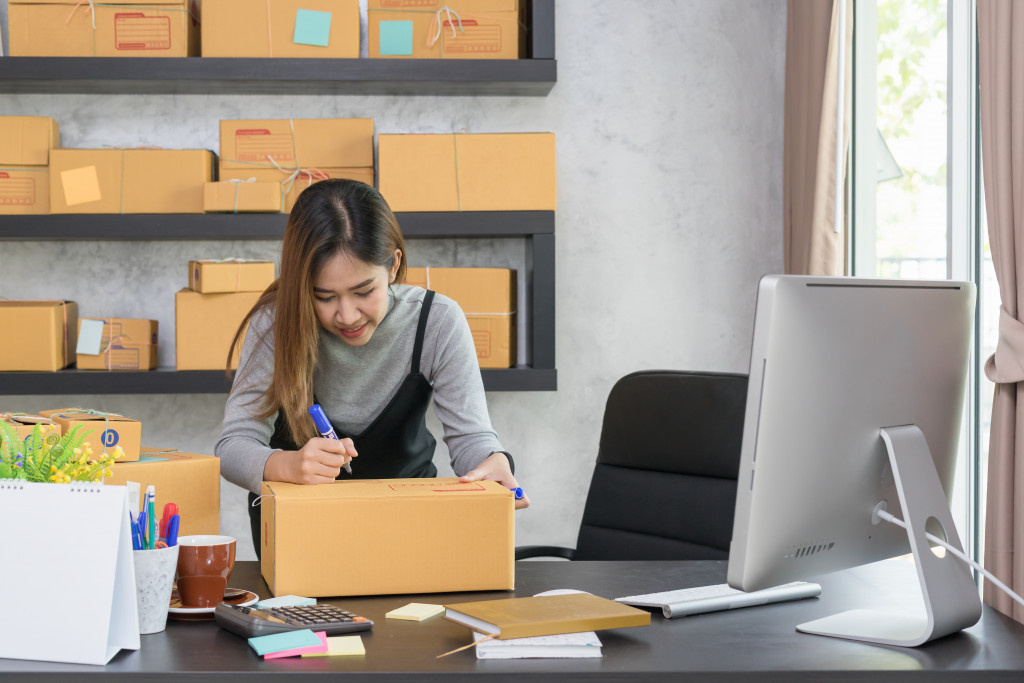 woman writing on box